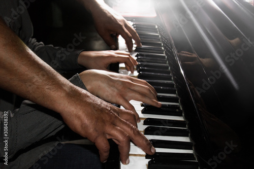 Obraz na plátně  playing four male hands on the piano