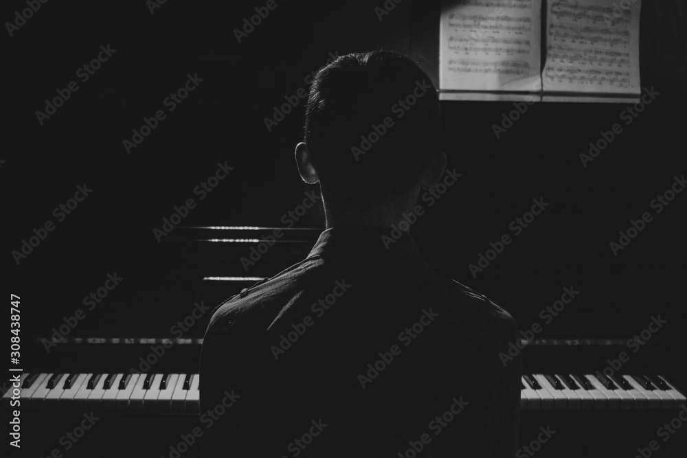 Fototapeta Silhouette of a young man sitting at the piano. The boy emotionally plays the keyboard in a music school. student learns to play. hands of a pianist. black and white photography.