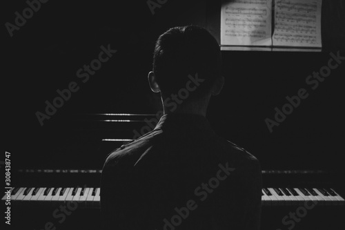 Silhouette of a young man sitting at the piano. The boy emotionally plays the keyboard in a music school. student learns to play. hands of a pianist. black and white photography. - 308438747