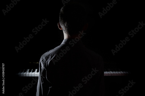 Fototapeta Silhouette of a young man sitting at the piano. The boy emotionally plays the keyboard in a music school. student learns to play. hands of a pianist. black and white photography. obraz