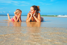 Happy People Have Fun In Sea Surf On White Sand Beach. Young Mother With Child Lying In Water Pool. Travel Lifestyle, Swimming Activities In Family Summer Camp. Vacations With Kids On Tropical Island.