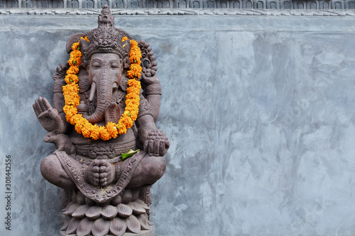fototapeta na szkło Ganesha sitting in meditating yoga pose in front of hindu temple. Decorated for religious festival by orange flowers garland, ceremonial offering. Balinese travel background. Bali island art, culture.
