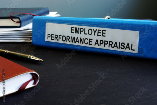Photo Folder with employee performance appraisal on the desk.