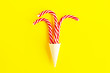 canvas print picture - Christmas or New Year creative still life, flat lay. Three Christmas canes in a waffle cone for ice cream on a bright yellow background. Holiday concept, greeting card design.