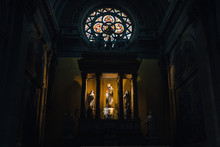 Five Religious Ancient Cultures Illuminated By Dim Light In A Dark Church Hall In Annecy, France. Photography Of Museum Hall With Colored Stained-glass Window With Stucco Molding And Wall Carvings.