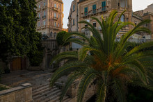 Palm Tree Near The Fountain Arethusa And Cityscape Of The Narrow Street In The Ortygia Island In The Province Of Syracuse In Sicily, South Italy