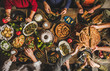 Traditional Turkish family celebration dinner. Flat-lay of people eating Turkish salads, cooked vegetables, meze starters and borek pie and drinking raki drink, top view. Middle Eastern cuisine