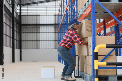 Fotografía Asian worker man hurt his back .lift heavy box in factory