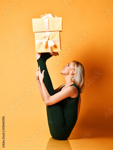 Smiling sporty girl does yoga asana stretching exercise holds New Year Christmas gifts boxes on her feet - 308463196