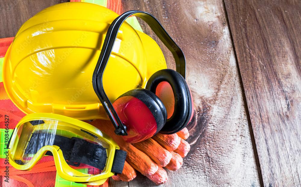 Fotografie, Obraz Standard construction safety equipment set on old wooden background including helmet, glasses, glove,  ear defenders and cloth
