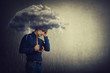 Pessimistic man, standing under rain, suffering anxiety as holding an umbrella thunderstorm cloud over head. Concept of memory loss and dementia disease. Alzheimer's losing brain and memory function.