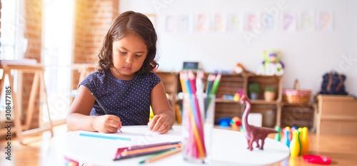 Obraz Beautiful toddler girl drawing cute draw using colored pencils at kindergarten - fototapety do salonu