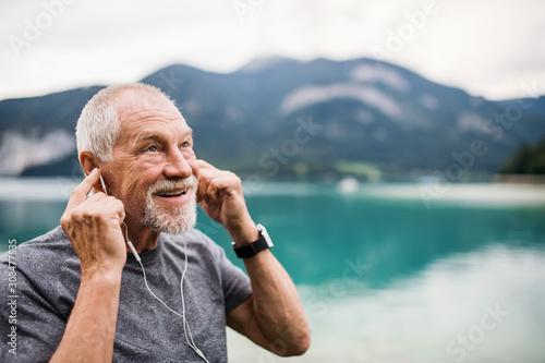 Fototapeta Senior man with earphones standing by lake in nature, listening to music. obraz