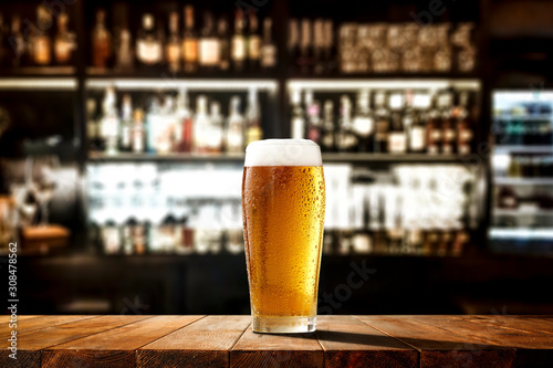 Glass of beer on wooden board and blurred bar background Fotobehang