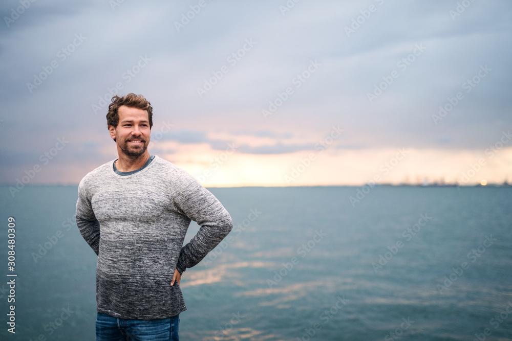 Fototapeta Mature man standing outdoors on beach at dusk. Copy space.