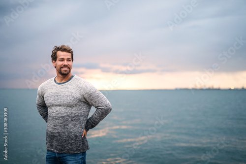 Mature man standing outdoors on beach at dusk. Copy space. - 308480309