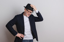 Portrait Of A Senior Man With Hat And Glasses In A Studio.