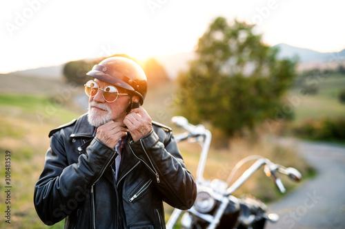 Obraz na płótnie A senior man traveller with motorbike in countryside, putting on helmet