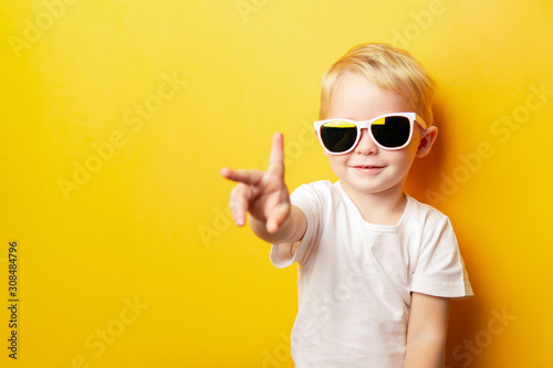 Canvastavla  Portrait of cheerful little boy in a white t-shirt wearing sunglasses and lookin