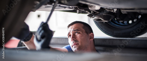 Auto mechanic repairer checking condition under car on vehicle lift