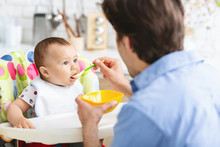 Father Feeding His Curious Baby Son At Kitchen Interior