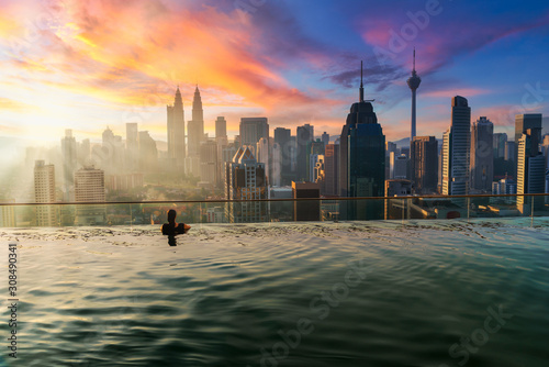 Canvas Prints Kuala Lumpur Asian businesswoman relax in swimming pool on roof top behind beautiful city view kuala lumpur in sunrise sky morning, Malaysia