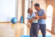 Leinwanddruck Bild - Middle age beautiful sporty couple smiling happy. Standing with smile on face hugging at gym