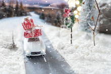 Miniature Classic Car Carrying A Christmas Gifts On Winter Landscape