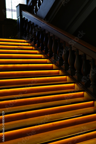 Illuminated wooden stairs with baluster railing and orange LED lights in the dark Wallpaper Mural