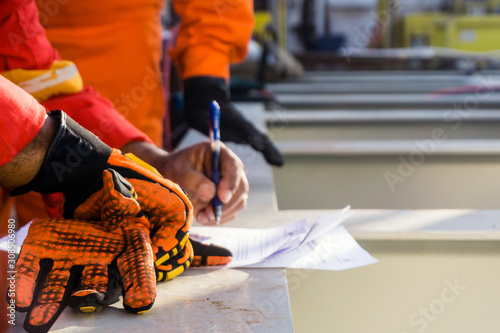 Fotografia, Obraz A supervisor signed a pre-job checklist on board a construction work barge prior