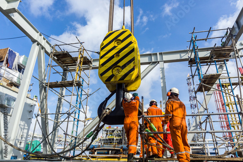 Wallpaper Mural Offshore workers performing inspection to a crane hook and rigging arrangement p