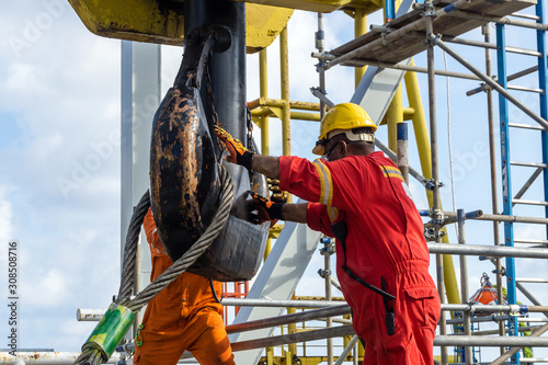 Photo Offshore workers performing inspection to a crane hook and rigging arrangement p