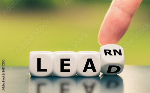 Fototapety, obrazy: Learn and Lead. Hand turns a dice and changes the word