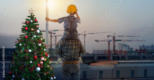 Asian boy on father's shoulders near Christmas tree with background of new high buildings and silhouette construction cranes of evening sunset, father and son on Christmas time