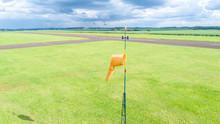 Orange Windsock Wind Sock On The Aerodrome, Sugar Cane Plantation Background.