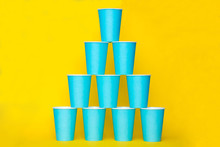 Pyramid Of Blue Paper Disposable Cups On Yellow Background. Set For Party. Copy, Empty Space For Text