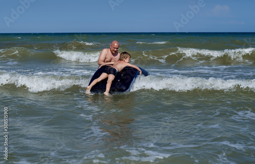 Photo father with son on an airbed at sea
