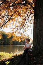 Little Girl Sitting Under Autu...