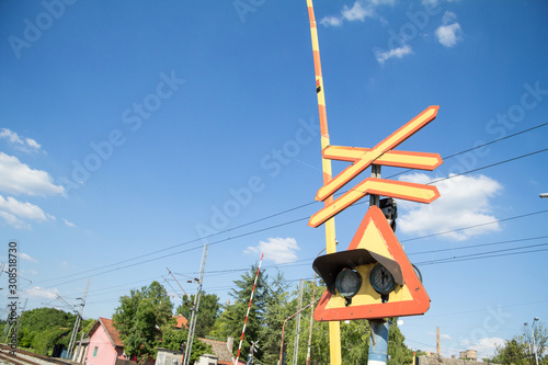 Valokuvatapetti Level crossing sign, called crossbuck, saltire or Saint Andrews cross, standing on a road which crosses a railway track in Pancevo, Serbia, with a barrier and traffic lights
