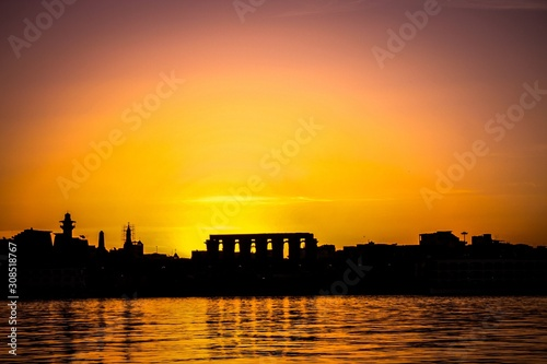 Fotografering  Breathtaking warm scenery of the sun setting over the city at the seashore in Ka