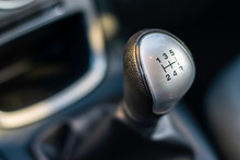 Gear Level For A Manual Transmission Vehicle, Showing Gears One Through To Five Including Reverse.  Background Blurred For Contrast.