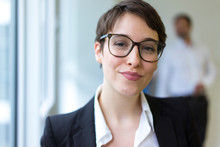 Portait Of Confident Young Businesswoman With Man In Background