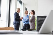 Three Businesswomen Talking At...