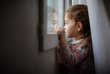 Side View Of Young Girl Looking Outside Window At Rain