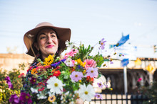 Happy Woman In An Urban Garden With Flowers