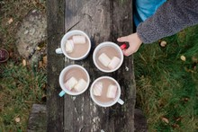 Hot Chocolate And Marshmallows On A Bench Outside With A Boy's Hand
