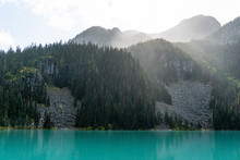 The Sun Shines Through Rain And Clouds Above Joffre Lake.