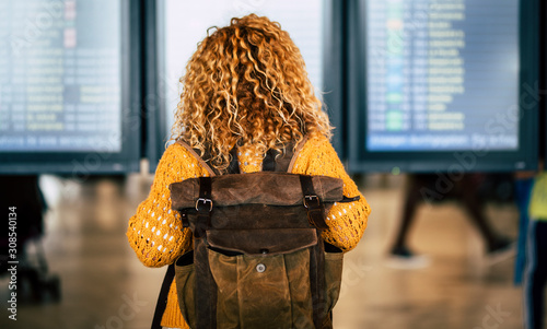 Obraz Blonde curly lady with backpack viewed from back looking the display with flights and timing at the airport - travel lifestyle and wanderlust activity - deleted flight concept - fototapety do salonu