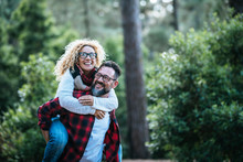 Happy And Cheerful Caucasian People Couple Having Fun Together In Friendship And Relationship - Middle Afe Woman And Man - Carrying The Lady In The Outdoor Leisure Activity With Green Forest