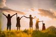 canvas print picture - The silhouette of the children holding hands, enjoying the sunset, a group of friends cheering and arms raised in the orange sky and the mountains behind Friendship concept